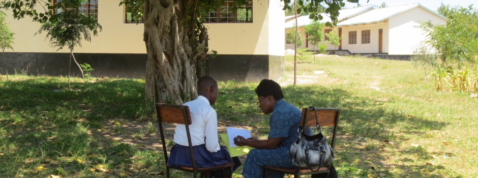 Study nurse interviewing study participant outside a school in Mwanza, Tanzania